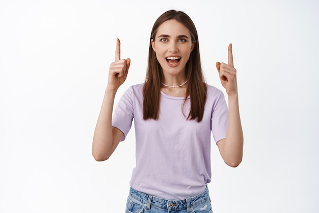 Mulher jovem sorridente apontando para um lugar olha para cima em pé com uma camiseta branca
