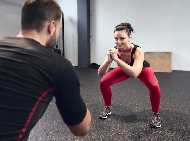 Mulher jovem sorridente, aquecendo com seu personal trainer na academia