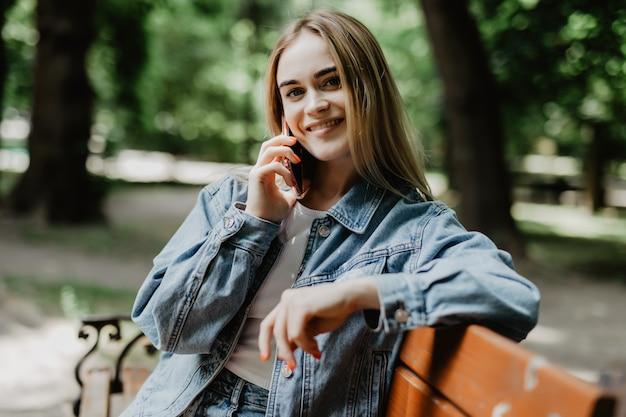 Mulher jovem sorridente chamando em smartphone na rua da cidade