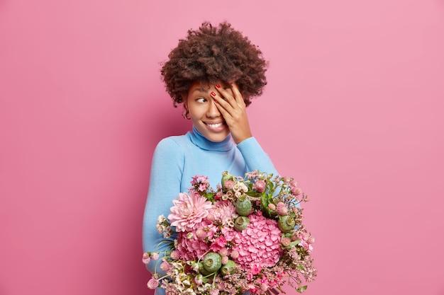 Mulher jovem sorridente com cabelo encaracolado cobre o rosto e desvia o olhar alegremente segurando um buquê de flores recebido da pessoa amada aproveitando o tempo de primavera isolado sobre a parede rosa