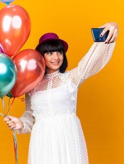 Mulher jovem sorridente com chapéu de festa segurando balões tirando selfie na parede laranja