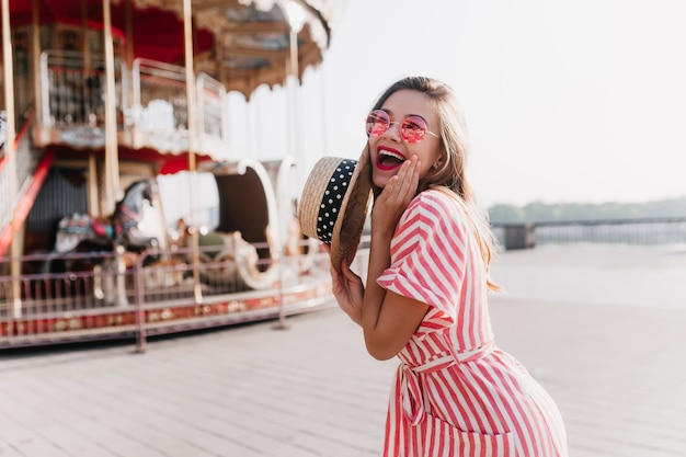 Mulher jovem sorridente com chapéu de palha vintage, posando no parque de diversões. linda garota loira com vestido listrado, aproveitando o fim de semana de verão ao ar livre.