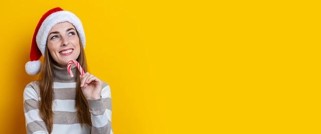 Mulher jovem sorridente com chapéu de papai noel com doces de natal em fundo amarelo. bandeira.