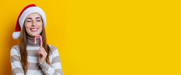 Mulher jovem sorridente com chapéu de papai noel com os olhos fechados com doces de natal em fundo amarelo. bandeira.