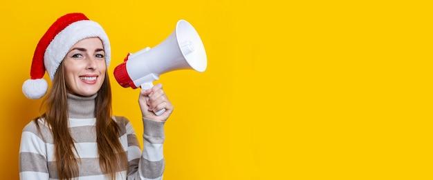 Mulher jovem sorridente com chapéu de papai noel com um megafone em um fundo amarelo. bandeira.