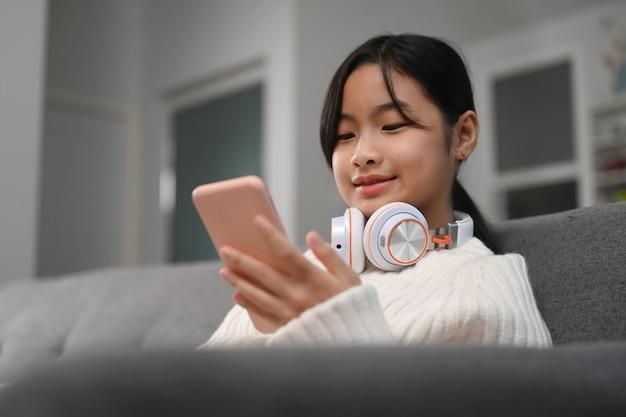 Mulher jovem sorridente com fone de ouvido usando telefone celular no sofá de uma casa.