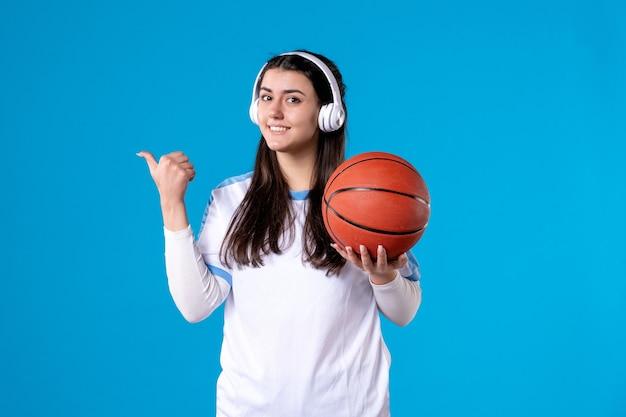 Mulher jovem sorridente com fones de ouvido segurando uma bola de basquete