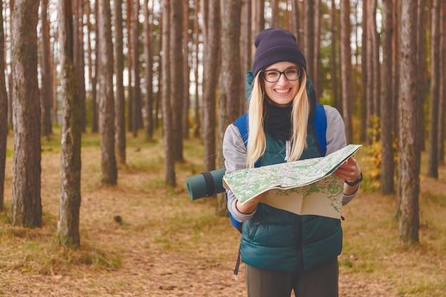 Mulher jovem sorridente com mapa de viagem e mochila na floresta de pinheiros