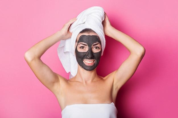 Mulher jovem sorridente com máscara facial e toalha na cabeça em um fundo rosa.