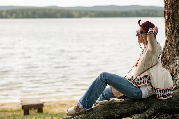 Mulher jovem sorridente com óculos e blusa hippie sentada na árvore e segurando um chapéu enquanto aproveita o vento perto do lago