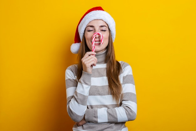 Mulher jovem sorridente com os olhos fechados com doces de natal no nariz contra um fundo amarelo.
