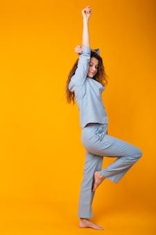 Mulher jovem sorridente com pijama em casa, posando enquanto descansava em casa, isolada na parede amarela