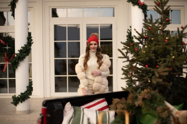 Mulher jovem sorridente com roupas quentes de inverno e caminhando perto de casa