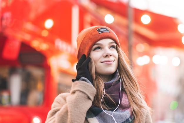 Mulher jovem sorridente com roupas quentes e um smartphone nas mãos ouve música nos fones de ouvido e olha de lado no fundo de um ônibus turístico vermelho
