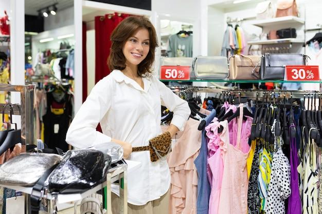 Mulher jovem sorridente com saco de cinto na cintura fica na loja de acessórios