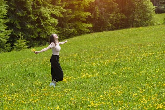 Mulher jovem sorridente com um buquê está girando em um campo de flores