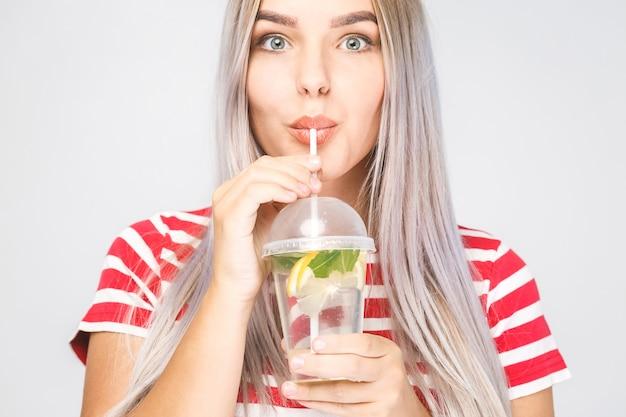 Mulher jovem sorridente com um copo de água com limão