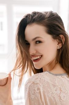 Mulher jovem sorridente com uma xícara de café da manhã. publicidade de energia positiva