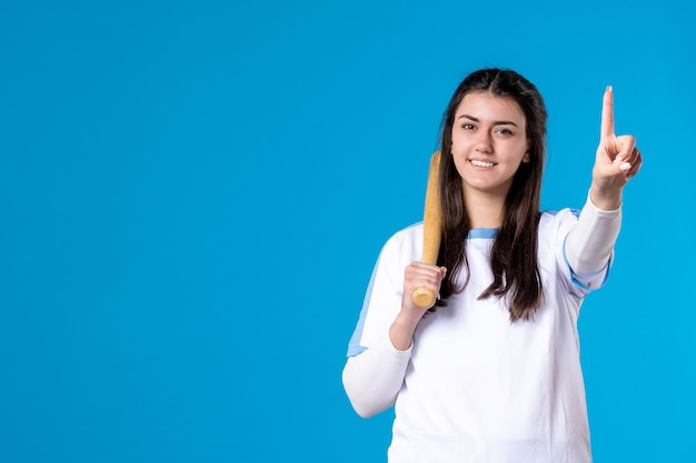 Mulher jovem sorridente com vista frontal com taco de beisebol
