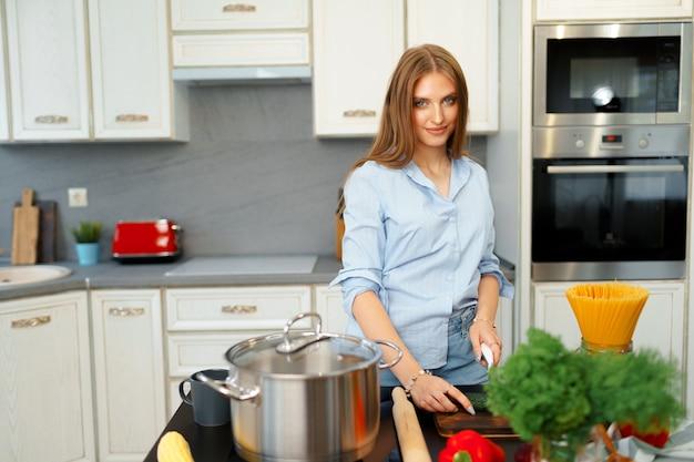 Mulher jovem sorridente cortando legumes para salada na cozinha