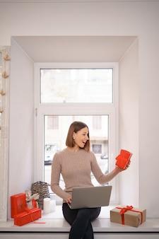 Mulher jovem sorridente cumprimentando amigos com natal em bate-papo por vídeo no laptop com caixas de presente