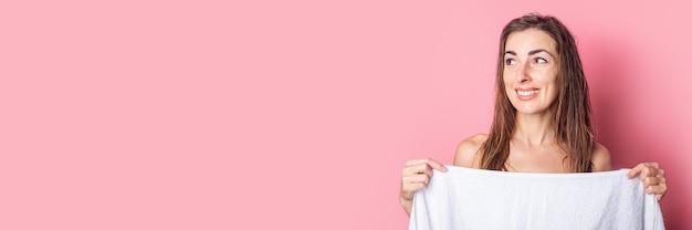 Mulher jovem sorridente depois do banho se cobre com uma toalha em um fundo rosa.