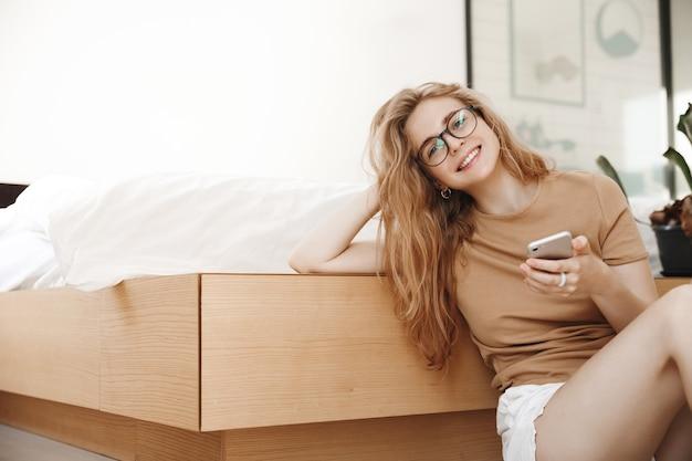 Mulher jovem sorridente descansando em casa com smartphone