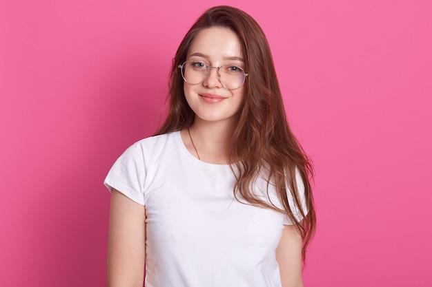 Mulher jovem sorridente despreocupada relaxada vestindo óculos e camiseta casual branca, tendo expressão facial positiva