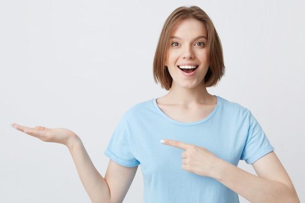 Mulher jovem sorridente e animada em camiseta azul apontando para o lado e segurando copyspace na palma da mão