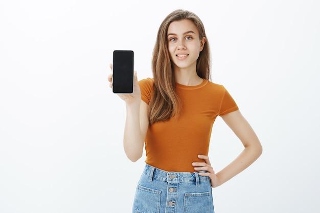 Mulher jovem sorridente e confiante dá conselhos, mostra a tela do smartphone, demonstra o aplicativo ou a loja