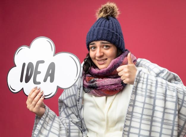 Mulher jovem sorridente e doente usando um manto de inverno, chapéu e lenço embrulhado em xadrez segurando uma bolha de ideia, olhando para a frente, mostrando o polegar isolado na parede rosa
