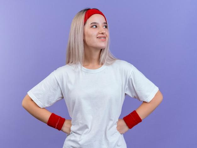 Mulher jovem sorridente e esportiva com aparelho ortodôntico usando bandana e pulseiras coloca as mãos na cintura olhando para o lado isolado na parede roxa