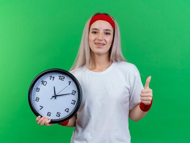 Mulher jovem sorridente e esportiva com aparelho usando fita para a cabeça e pulseiras segurando o relógio e os polegares para cima, isolados na parede verde