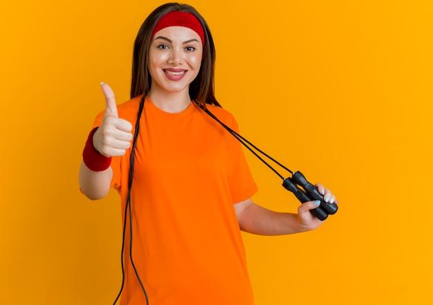 Mulher jovem sorridente e esportiva usando bandana e pulseiras com corda de pular em volta do pescoço agarrando a corda de pular olhando aparecendo o polegar