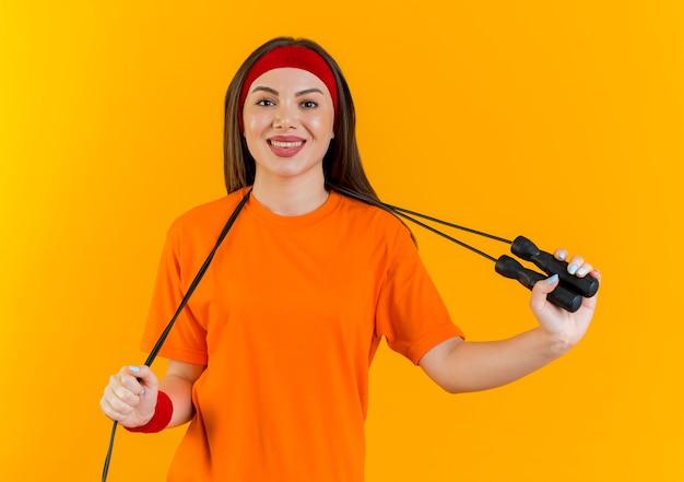 Mulher jovem sorridente e esportiva usando bandana e pulseiras com corda de pular em volta do pescoço, segurando a corda de pular