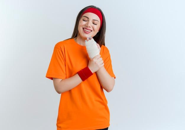 Mulher jovem sorridente e esportiva usando bandana e pulseiras segurando o pulso ferido envolto em bandagem com os olhos fechados, isolado na parede branca com espaço de cópia