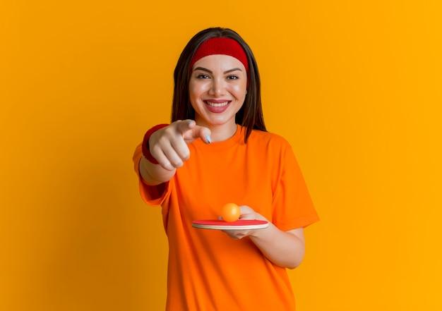 Mulher jovem sorridente e esportiva usando bandana e pulseiras segurando uma raquete de pingue-pongue com uma bola olhando e apontando isolada na parede laranja com espaço de cópia
