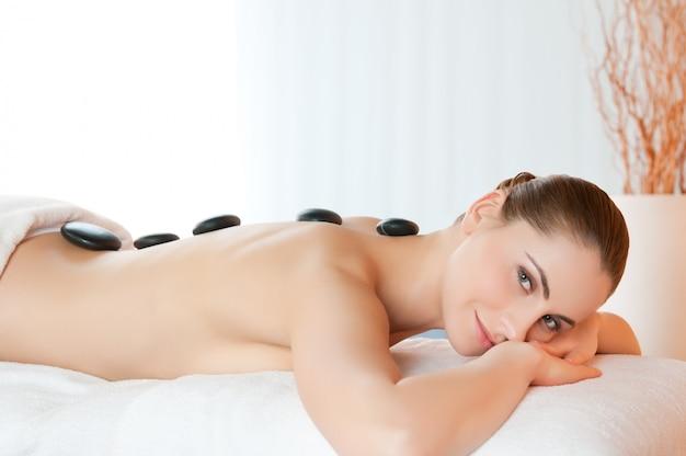 Mulher jovem sorridente e feliz deitada com pedras nas costas no centro de spa de beleza