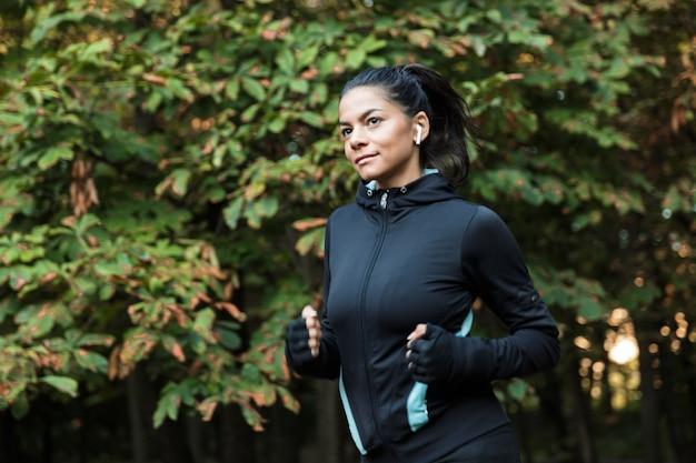 Mulher jovem sorridente e fitness correndo no parque, ouvindo música com fones de ouvido