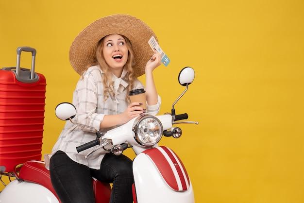 Mulher jovem sorridente e sonhadora usando chapéu e sentada na motocicleta segurando café e bilhete amarelo