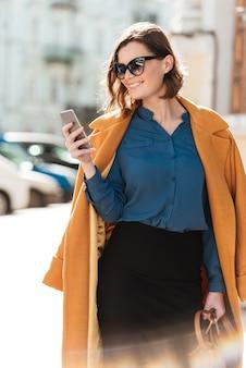 Mulher jovem sorridente em casaco e óculos de sol