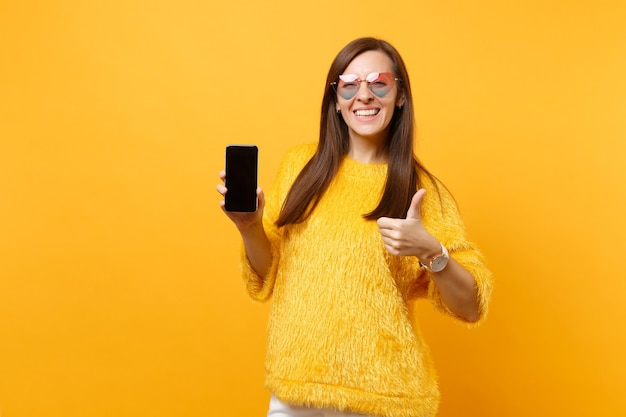 Mulher jovem sorridente em copos de coração aparecendo o polegar e segurando o telefone móvel com tela vazia preta em branco, isolada no fundo amarelo brilhante. pessoas sinceras emoções, estilo de vida. área de publicidade.
