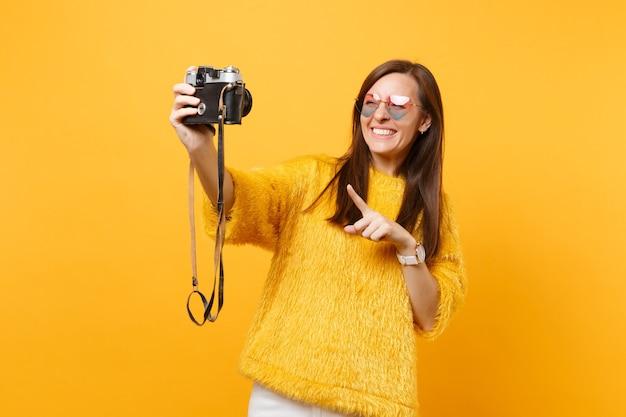 Mulher jovem sorridente em copos de coração fazendo selfie tiro na câmera fotográfica retro vintage, apontando o dedo indicador isolado em fundo amarelo. pessoas sinceras emoções, estilo de vida. área de publicidade.