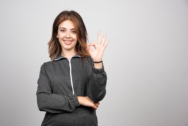 Mulher jovem sorridente em pé e mostrando gesticulando sinal de ok com os dedos.
