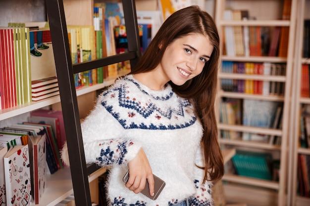 Mulher jovem sorridente em pé na estante de livros com o celular e olhando para a câmera