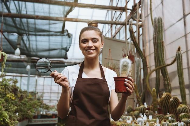 Mulher jovem sorridente em pé na estufa perto de plantas