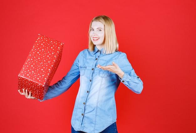 Mulher jovem sorridente em pé no vermelho segurando uma caixa de presente de aniversário