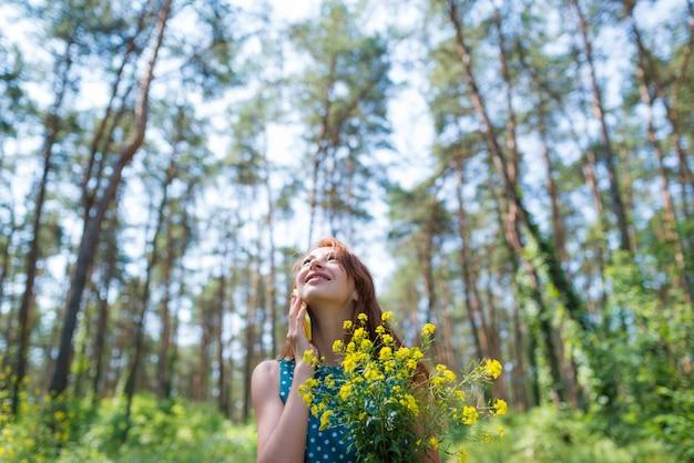 Mulher jovem sorridente em pé, segurando flores amarelas e olhando para o céu na floresta num dia ensolarado de verão. estar no conceito de natureza