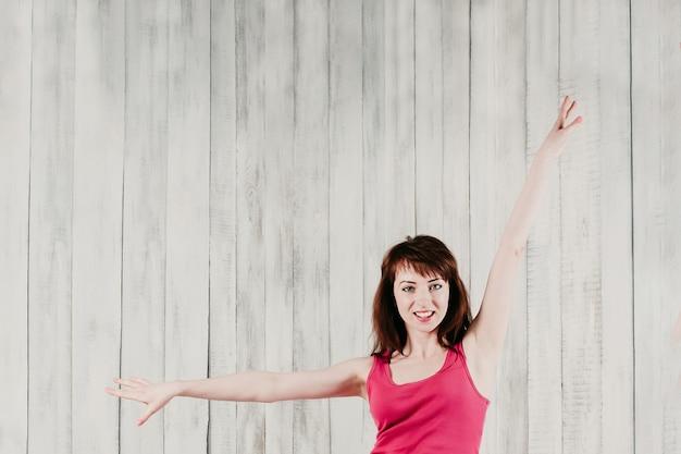 Mulher jovem sorridente em um top rosa fazendo exercícios