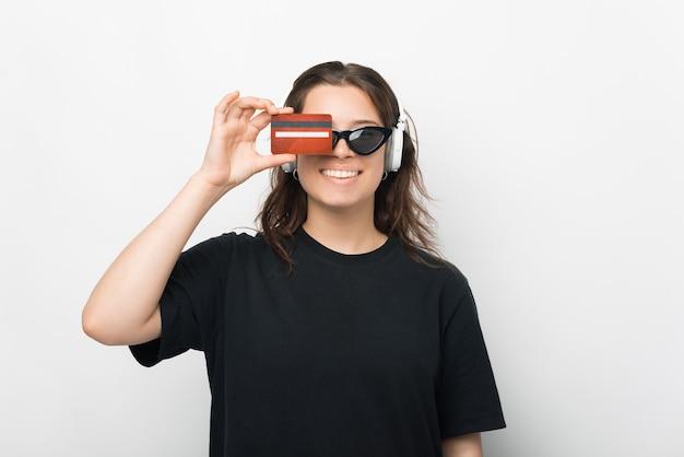 Mulher jovem sorridente em uma camiseta preta mostrando um cartão de crédito vermelho sobre fundo branco